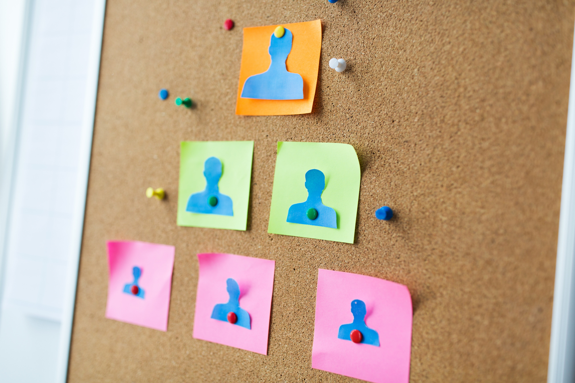 close up of paper human shapes on cork board with stickers and office pins